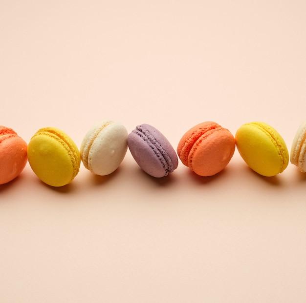 Круглые разноцветные запеченные макароны со сливками лежат в ряд на бежевой поверхности