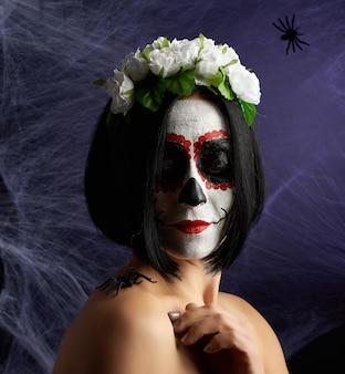 伝統的なメキシコの死のマスクを持つ美しい少女。