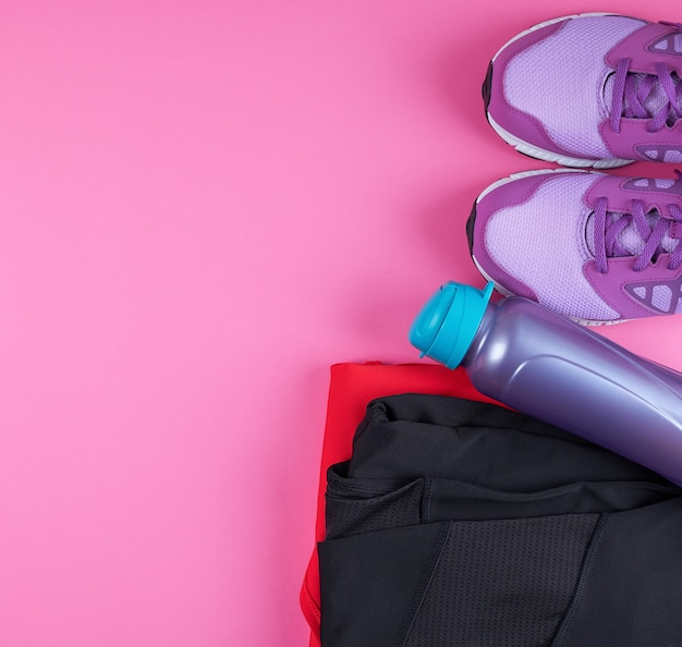 Розовые женские кроссовки, бутылка воды, одежда для спорта на розовой поверхности
