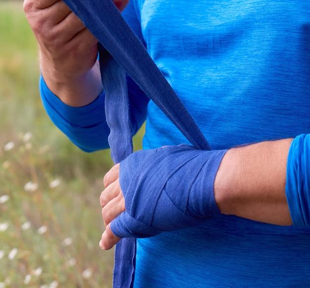Спортсмен встает и оборачивает руки в синий текстильный эластичный бинт перед тренировкой