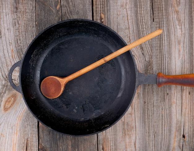 木のスプーンと木製ハンドル付きの空の黒い丸いフライパン