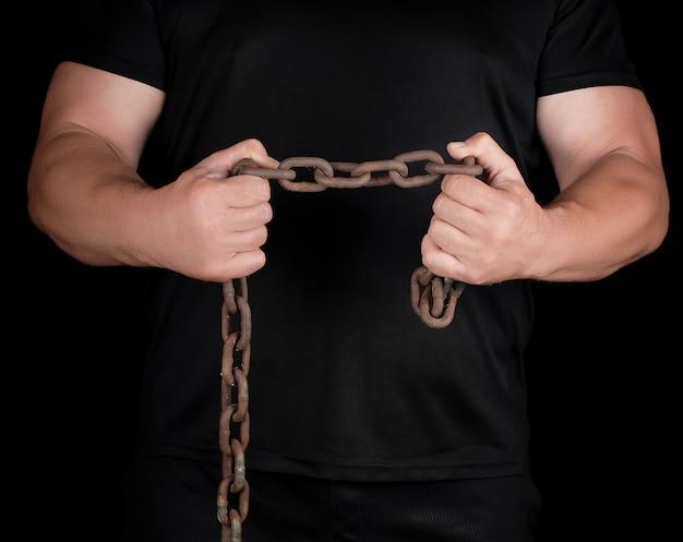 黒い服を着た成人男性は緊張した筋肉で直立し、さびた金属チェーンを保持しています