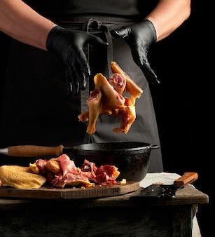 Шеф-повар в черной униформе и измельчающих латексных перчатках бросает нарезанную курицу в черную чугунную сковороду с деревянной ручкой