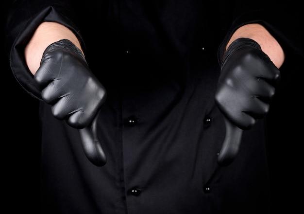 黒いラテックス手袋のシェフは好きではないジェスチャーを示しています