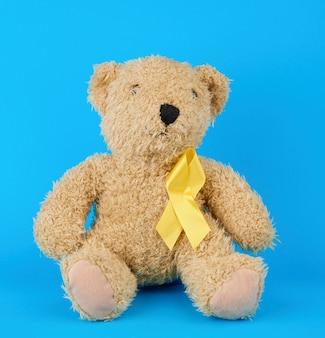 茶色のテディベアが座っているし、彼の足で青い背景に黄色のシルクリボンを保持