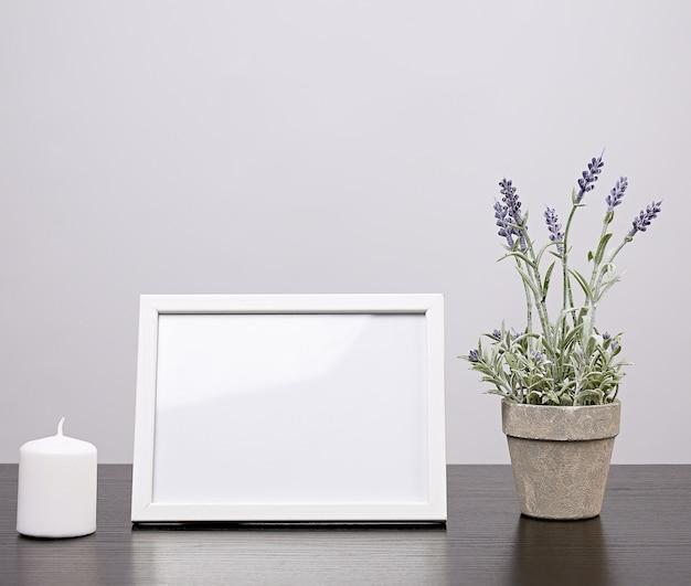 空の白いフレーム、花と黒いテーブルの上のキャンドルで植木鉢