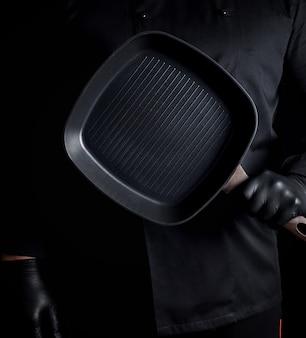 空の正方形グリルパンを保持している黒い制服と黒いラテックス手袋のシェフ
