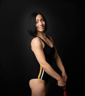 Юная гимнастка кавказской внешности с черными волосами плетет красные атласные ленты