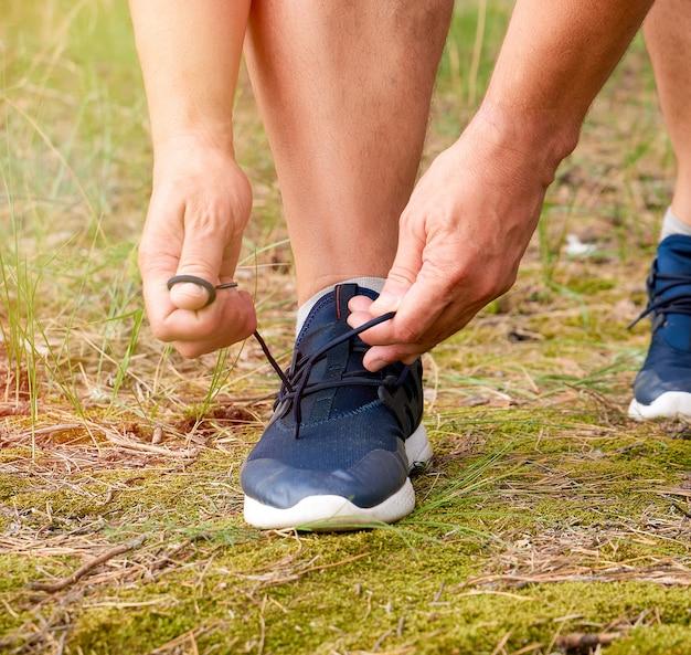 黒い制服を着た選手が身をかがめ、森の真ん中で青いスニーカーのひもを結ぶ