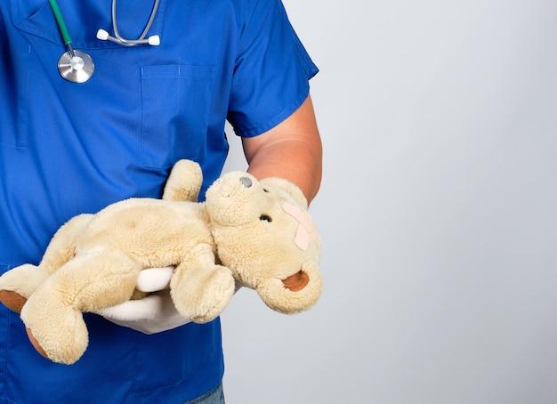 茶色のテディベアを保持している青い制服と白いラテックス手袋の医者