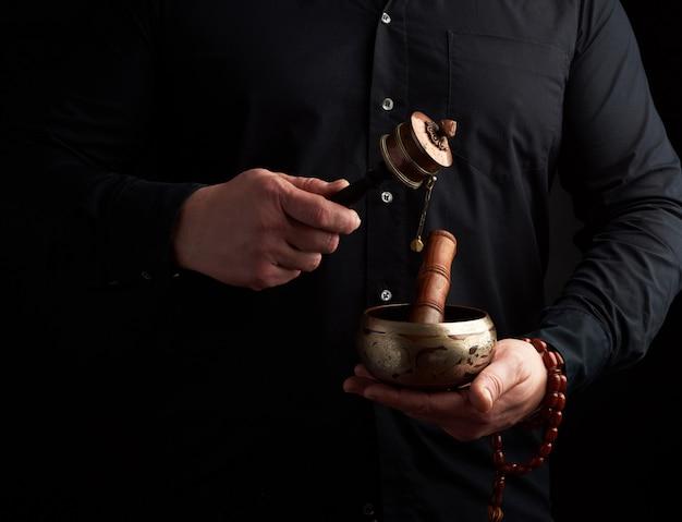 黒いシャツを着た男はチベットの真鍮の歌うボウルと木の棒を保持しています