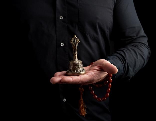黒いシャツを着た成人男性は、銅のチベットの儀式の鐘、低いキーを保持しています。