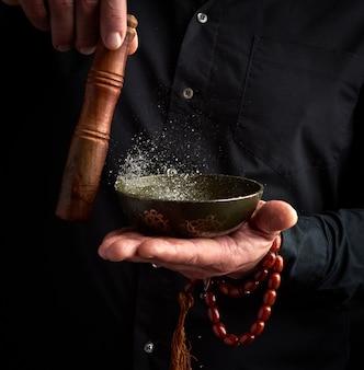 黒いシャツを着た大人の男が銅のチベットのボウルに木製の棒を回転させる