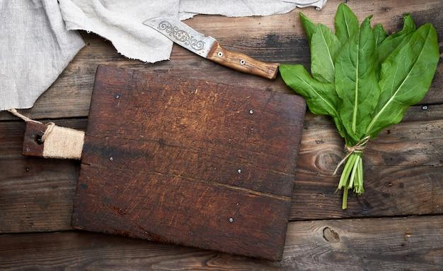 新鮮な緑スイバの束と古い茶色のまな板