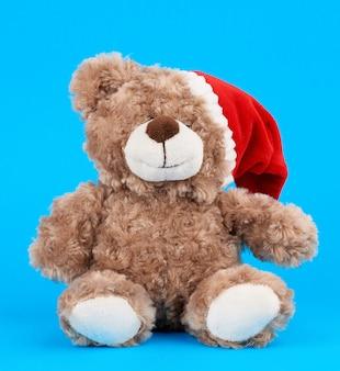 Маленький милый коричневый мишка с в красной шляпе рождество