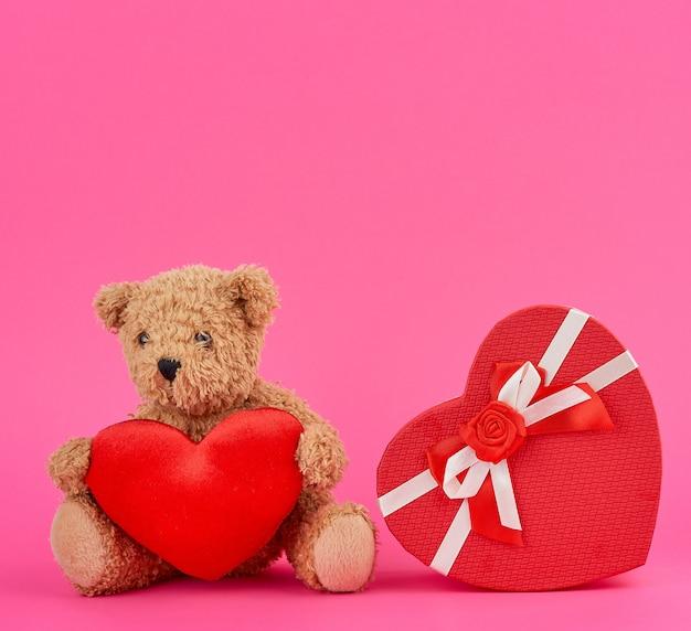 Милый коричневый мишка держит большое красное сердце и красную коробку