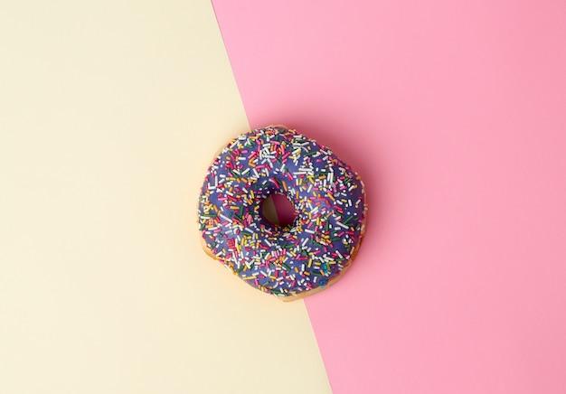 ピンク黄色の背景に色の砂糖を振りかけた丸焼きドーナツ