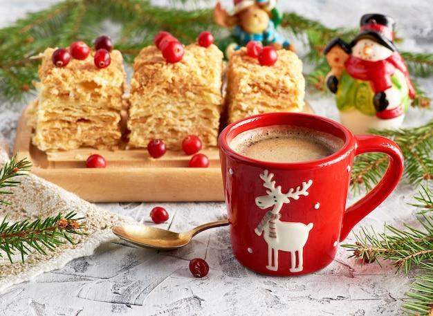 ブラックコーヒーとパフケーキナポレオンのスライスとバタークリームの赤いセラミックカップ