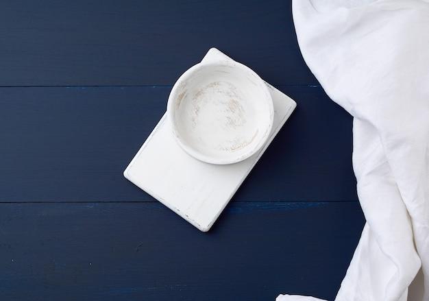 長方形の白いカッティングキッチンボードと空の丸皿