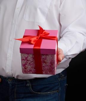 Взрослый мужчина в белой рубашке держит розовую подарочную картонную коробку с бантиком