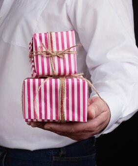 Взрослый мужчина в белой рубашке держит розовую подарочную картонную коробку