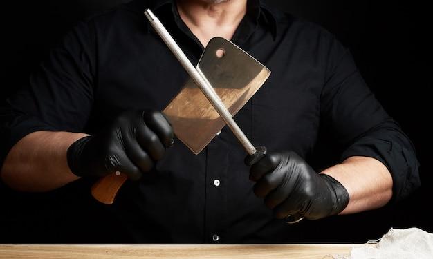 Шеф-повар в черной рубашке и черных латексных перчатках точит кухонный нож на железной точилке с ручкой