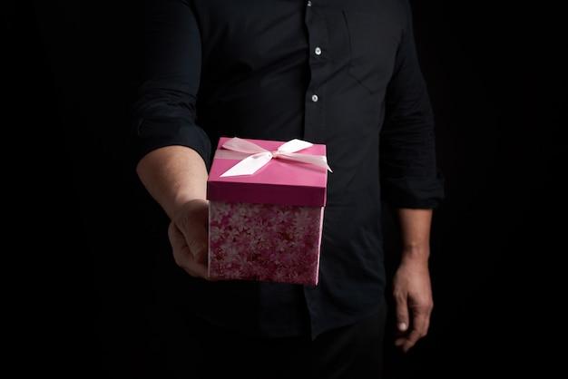 Взрослый мужчина в черной рубашке держит розовую квадратную коробку с завязанным бантом