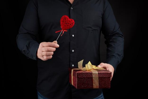 黒いシャツを着た成人男性は、黄金の弓で結ばれた赤い段ボール箱を手に持っています
