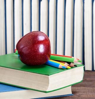 書籍のスタックの上に横たわる熟した赤いリンゴ