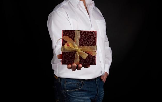 白いシャツを着た成人男性は、結び目のある黄金の弓で赤い四角の箱を保持します