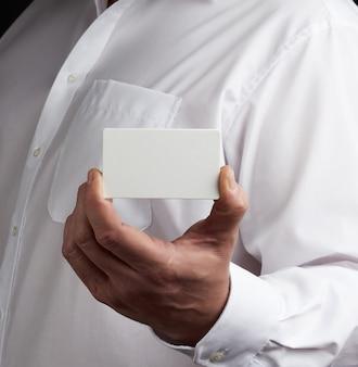 男性の手は長方形の空のホワイトペーパー名刺を保持します