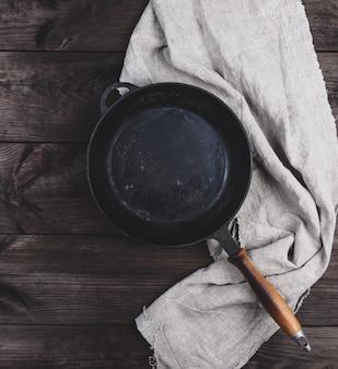 空の黒い丸型フライパン、木製の柄とグレーのリネンキッチンナプキン