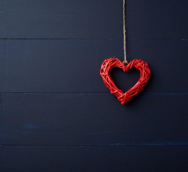 茶色のロープにぶら下がっている赤い枝編み細工品装飾的な心