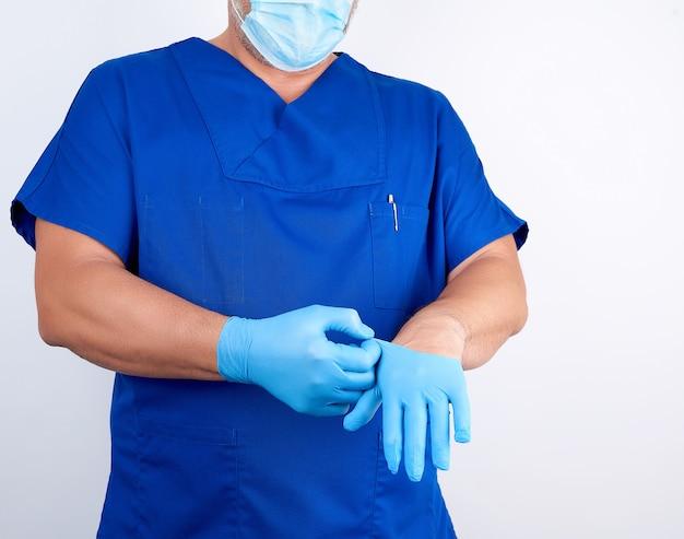 青い制服を着た男性医師は手術前に青い滅菌ラテックス手袋を彼の手に置きます