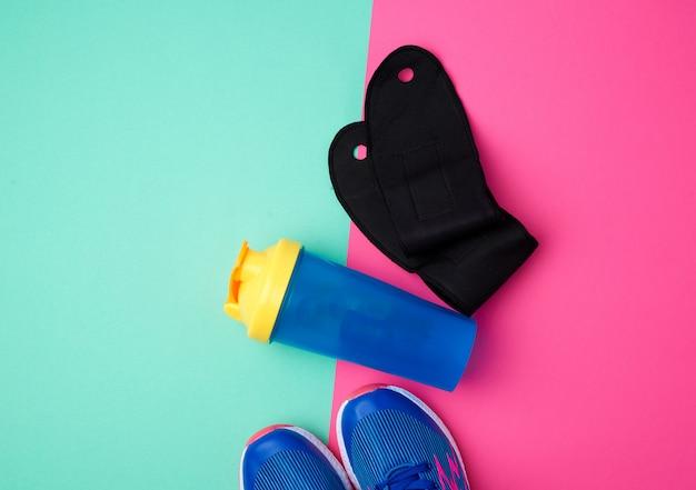 Пара спортивных кроссовок с синими шнурками, пластиковая бутылка с водой и черные перчатки