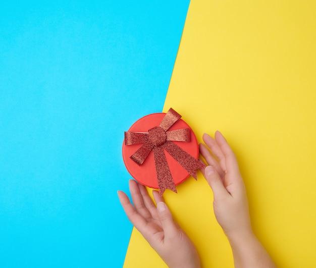 手は赤い弓で閉じた段ボール箱を保持します