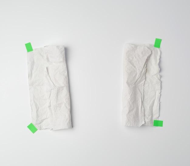 Мятый грязный белый кусок бумажного полотенца, склеенный зеленой липучкой