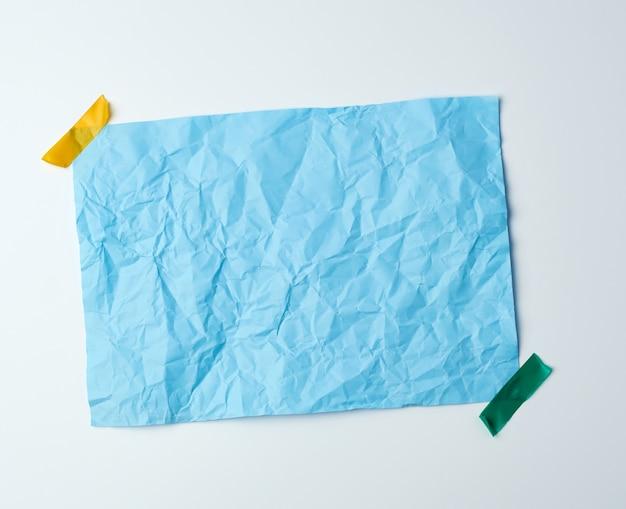Синий мятый лист бумаги, склеенный клейкой лентой