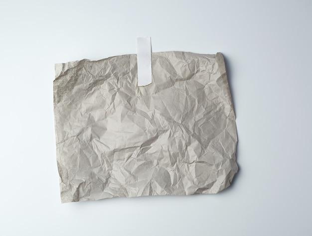 Серый мятый лист бумаги, склеенный белой клейкой лентой