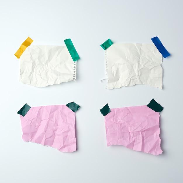 Чистые мятые листы бумаги, приклеенные резиновой лентой