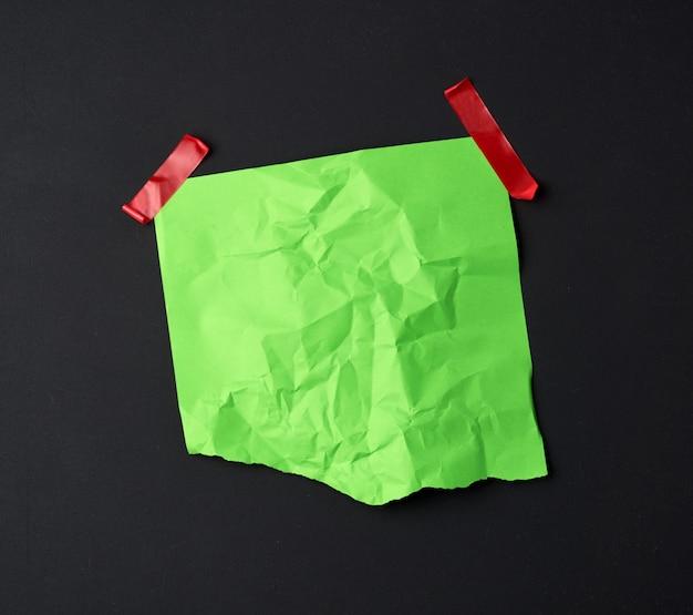 Зеленый мятый лист бумаги, наклеенный резиновой красной клейкой лентой