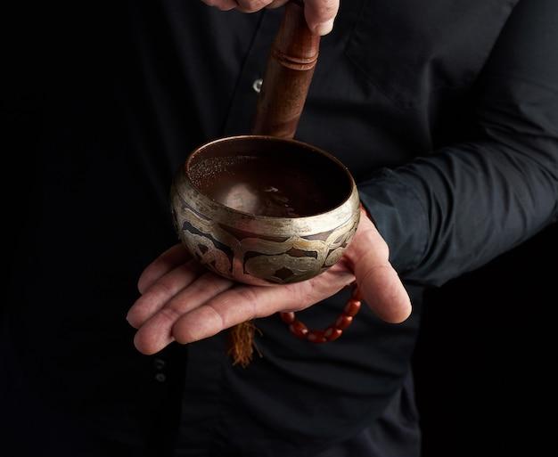 黒のシャツを着た男が銅のチベットボウルの周りに木製の棒を回転させる