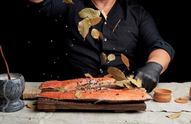 Взрослый мужчина в черной рубашке наливает белую грубую соль и сухой лавровый лист на свежее филе лосося