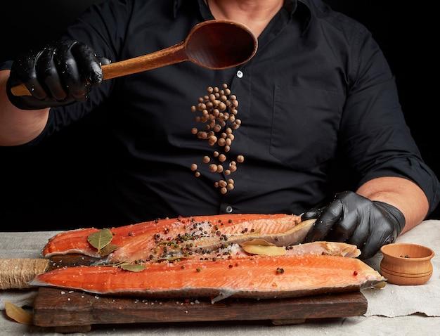 Шеф-повар в черной одежде и черных латексных перчатках льет душистый перец на нарезанную тушу свежей рыбы лосося
