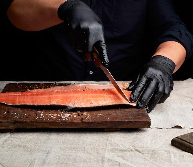 Шеф-повар в черной одежде и черных латексных перчатках режет свежее филе лосося на кусочки
