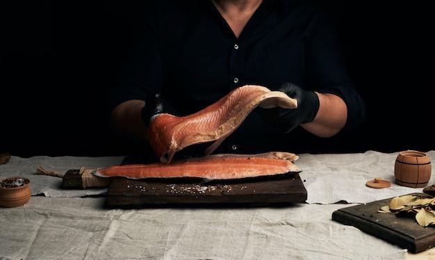 Шеф-повар в черной рубашке и черных латексных перчатках держит большой кусок филе лосося над столом