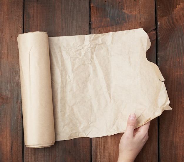 手は茶色の羊皮紙で展開ロールを保持します