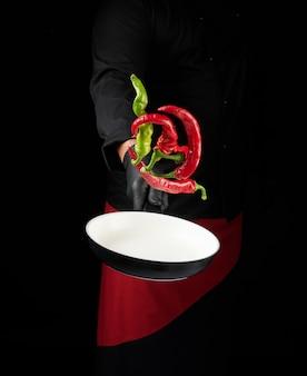 黒の制服と赤いエプロンのシェフは、新鮮な唐辛子と丸い鍋を保持しています