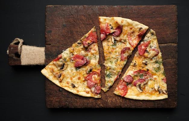 Запеченная пицца с копчеными колбасками, грибами, помидорами, сыром и укропом