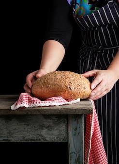 青の縞模様のエプロンの女性は、ひまわりの種と丸いライ麦パンを焼き彼女の手で保持します